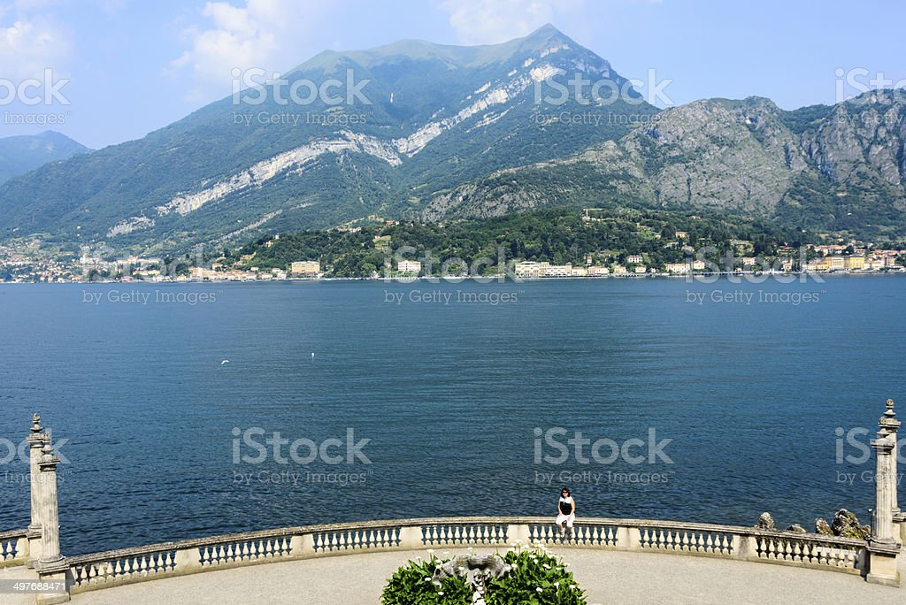 Woman sitting on fence at Lake Como, Italy royalty-free stock photo