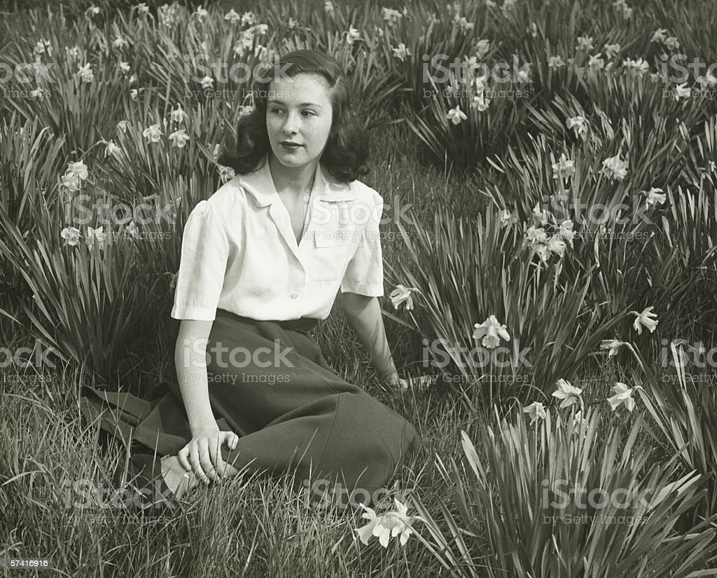 Woman sitting on grass among blooming daffodils, (B&W), (Portrait) royalty-free stock photo