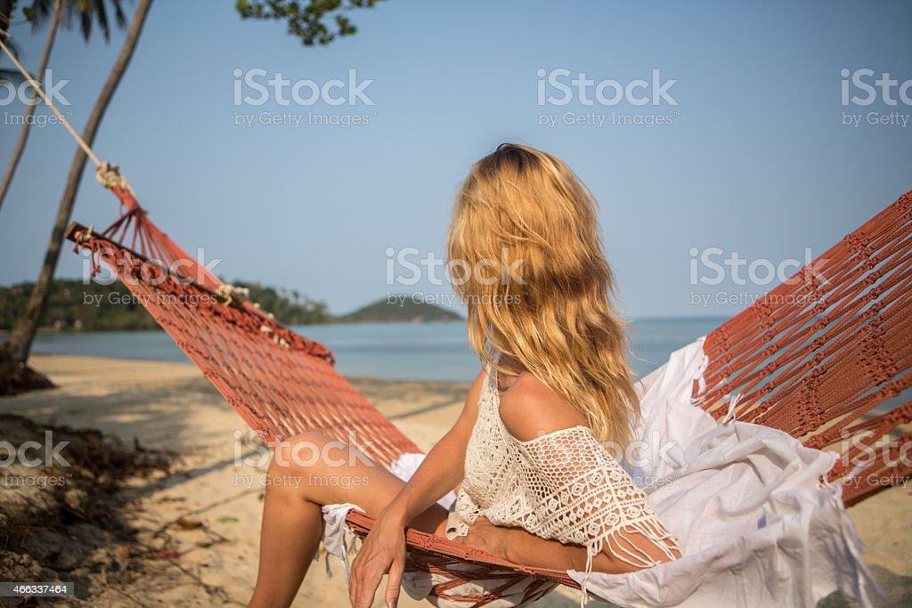Woman sitting on hammock-Exotic beach stock photo