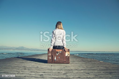 istock woman sitting on her suitcase waiting for the sunset 515672638