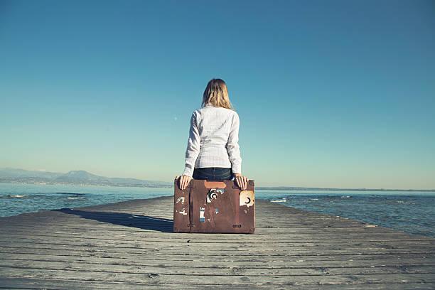 donna seduta sulla sua valigia in attesa per il tramonto - donna valigia solitudine foto e immagini stock