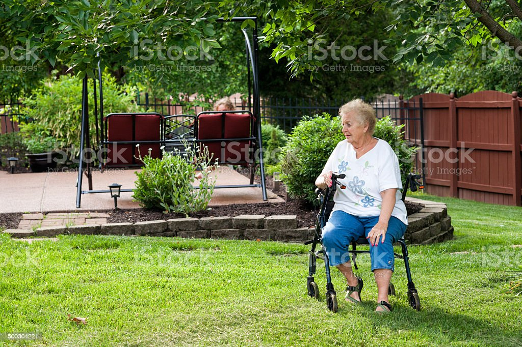 Woman sitting on her walker stock photo