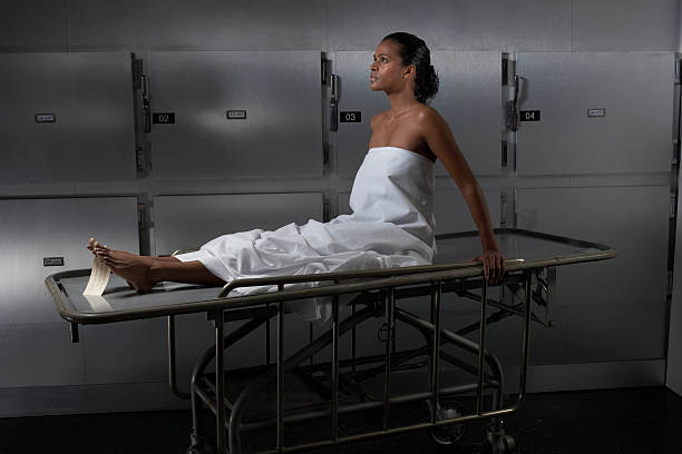 Woman sitting on hospital trolley, side view stock photo