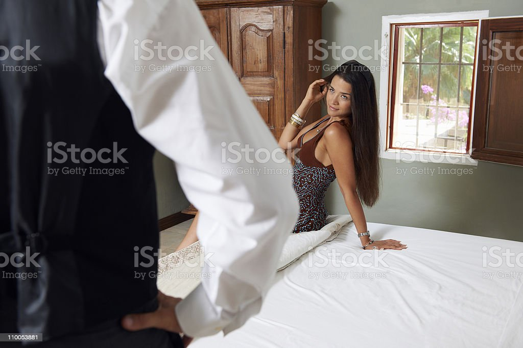 Woman sitting on hotel bed with waiter stock photo