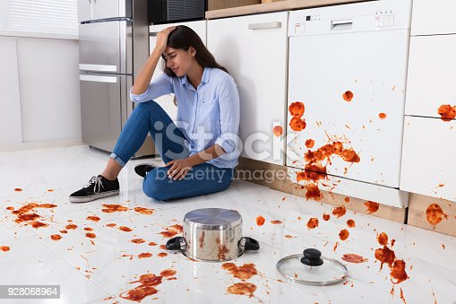 istock Woman Sitting On Kitchen Floor With Spilled Food 928068964