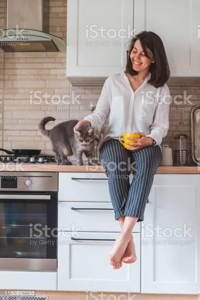 Woman sitting on kitchen table with cat drinking tea from yellow mug picture id1150892253?b=1&k=6&m=1150892253&s=612x612&h=yk6wts1ycfyy12nu8z1q6fqnsjhqiz jkuicjyadhya=