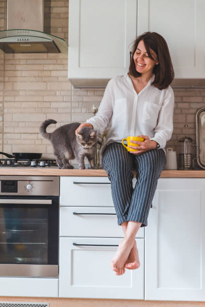 Woman sitting on kitchen table with cat drinking tea from yellow mug picture id1150892253?b=1&k=6&m=1150892253&s=612x612&w=0&h=i1kcqnwm89ow otporfolydlshvgomhls9r1vwacny0=