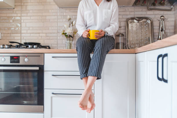 woman sitting on kitchen table with phone and yellow mug stock photo
