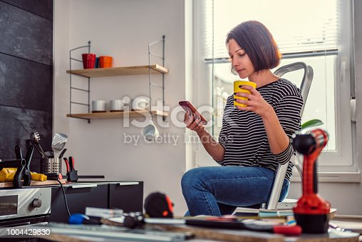 istock Woman sitting on ladder and using smart phone 1004429830