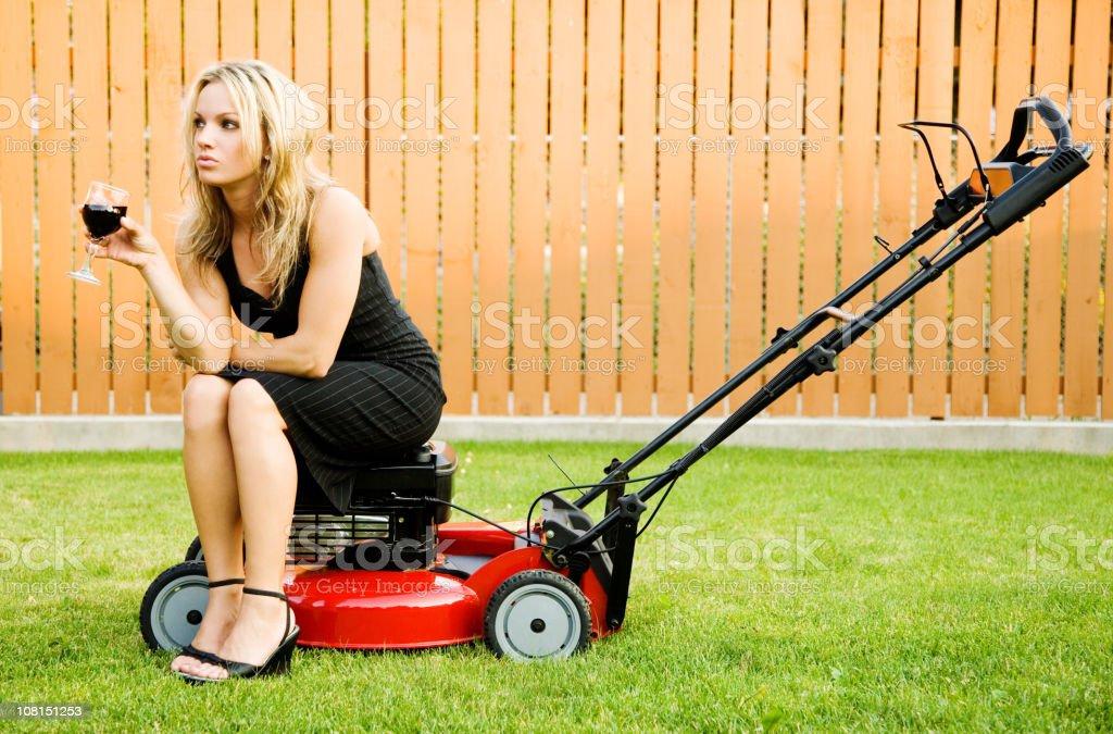 Woman Sitting on Lawnmower Drinking Wine stock photo