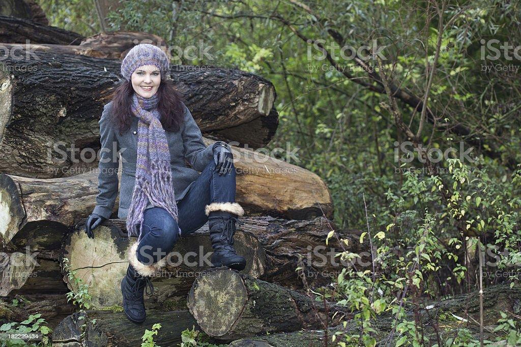 Woman sitting on logs stock photo