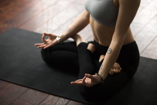 frau sitzt auf der matte in lotus posieren macht mudra, studio - buddhist tattoos stock-fotos und bilder