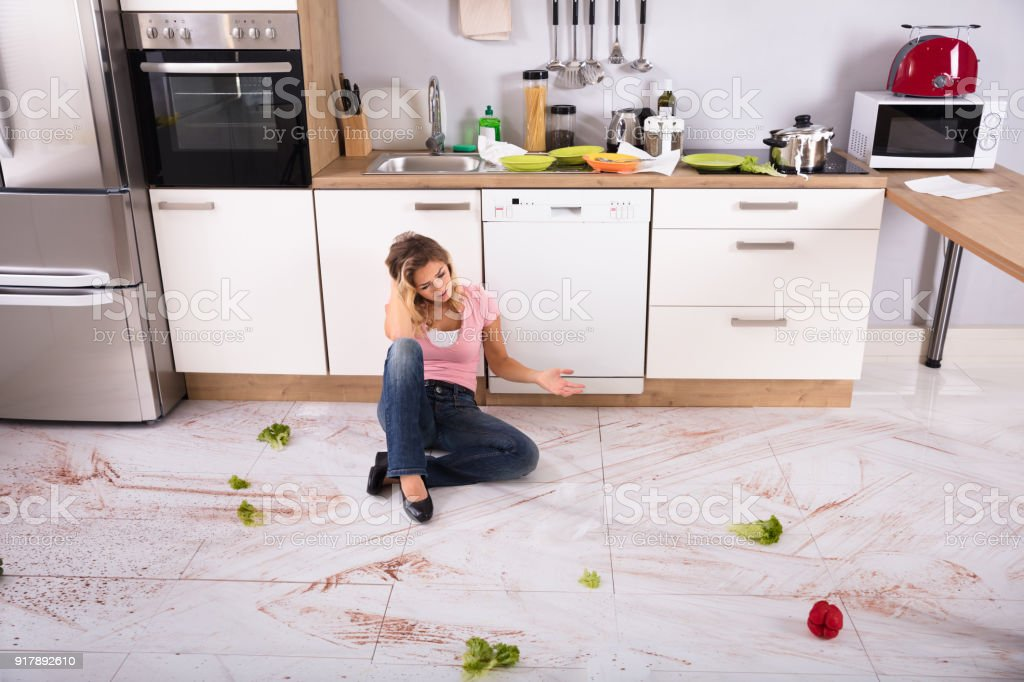 Unhappy Young Woman Sitting On Dirty Kitchen Floor At Home
