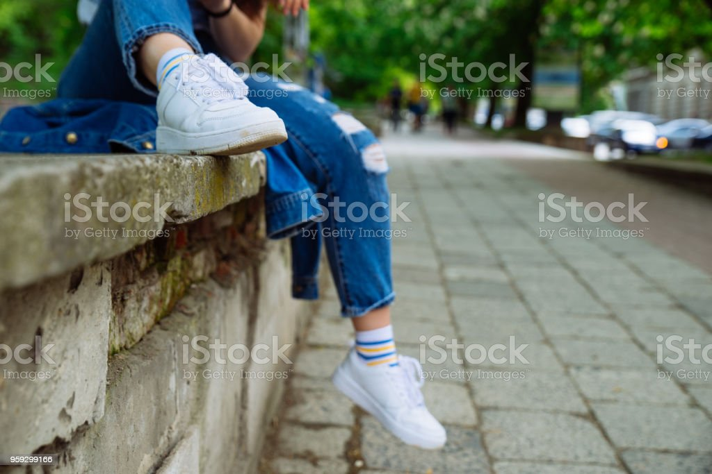 woman sitting on parapet at street. resting after walk. body part stock photo