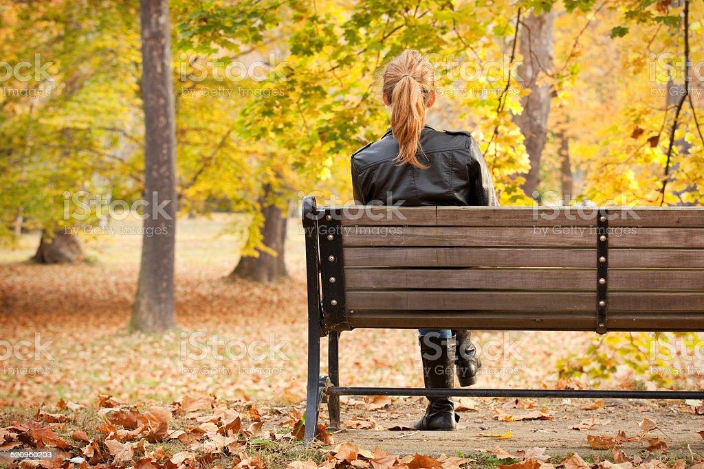 Femme assise sur le banc en profitant de la vue sur le parc en automne - Photo