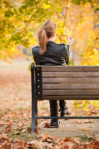 frau sitzt auf park bench holding herbst blatt - sitzbank schuhe stock-fotos und bilder