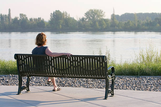 Woman sitting on park bench looking at river stock photo