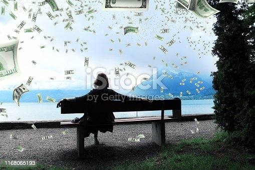 rear view of young adult woman sitting on park bench looking at view with flying large group of money over sky