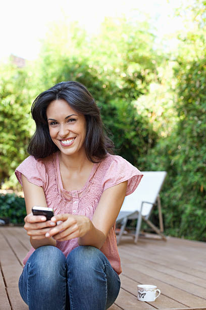 Woman sitting on patio holding cell phone stock photo