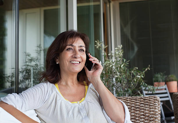 woman sitting on patio talking on cell phone - older woman phone stock photos and pictures
