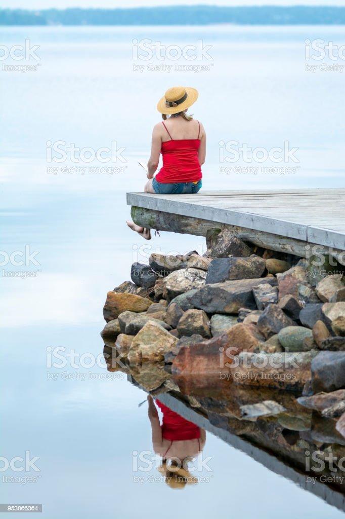 Woman sitting on pier at lake stock photo