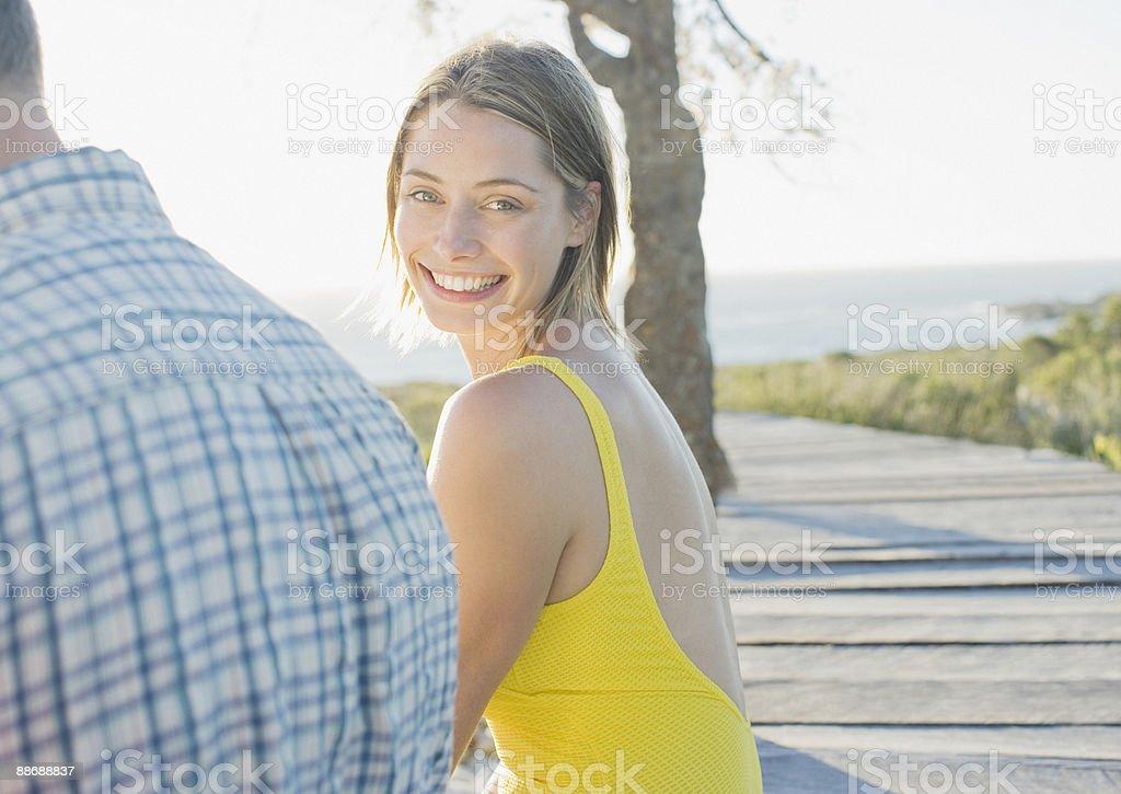 Woman sitting on pier near ocean royalty-free stock photo
