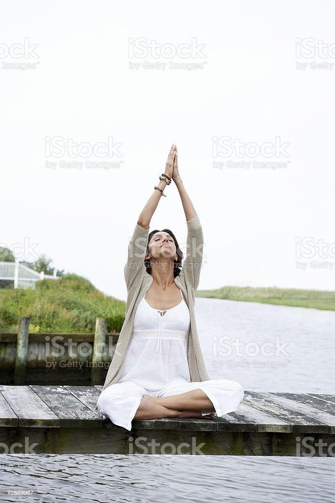 Mulher sentada no pier, esticar os braços foto de stock royalty-free