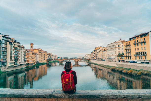 Woman sitting on Ponte Veccio and looking at view Young Caucasian woman sitting on Ponte Veccio in Florence  and looking at view, Italy florence italy stock pictures, royalty-free photos & images