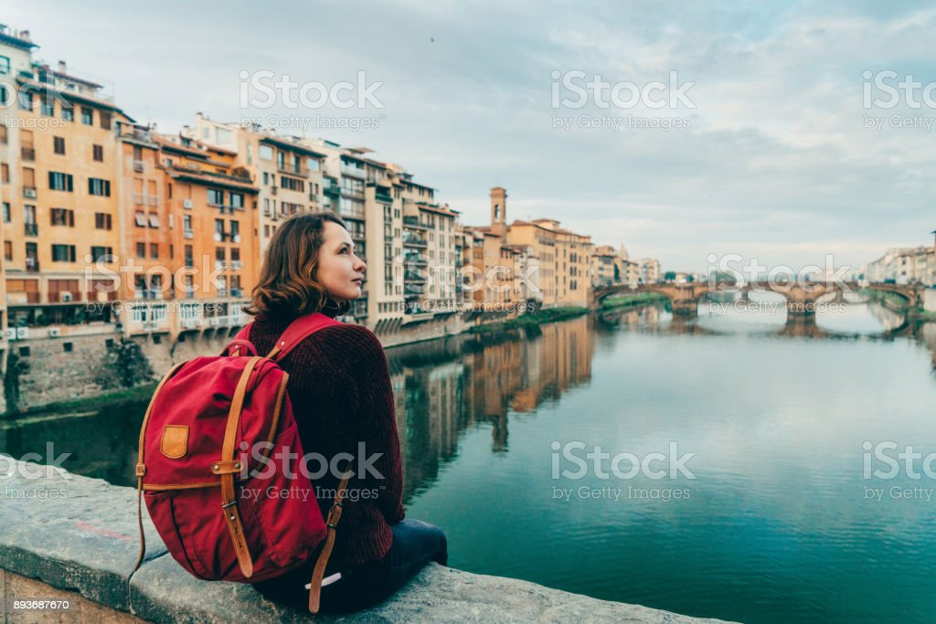 Woman sitting on Ponte Veccio and looking at view