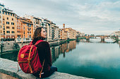 Young Caucasian woman sitting on Ponte Veccio in Florence  and looking at view, Italy