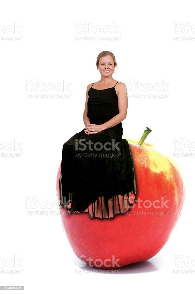 Woman Sitting on Red Delicious Apple with Nutrition Label stock photo