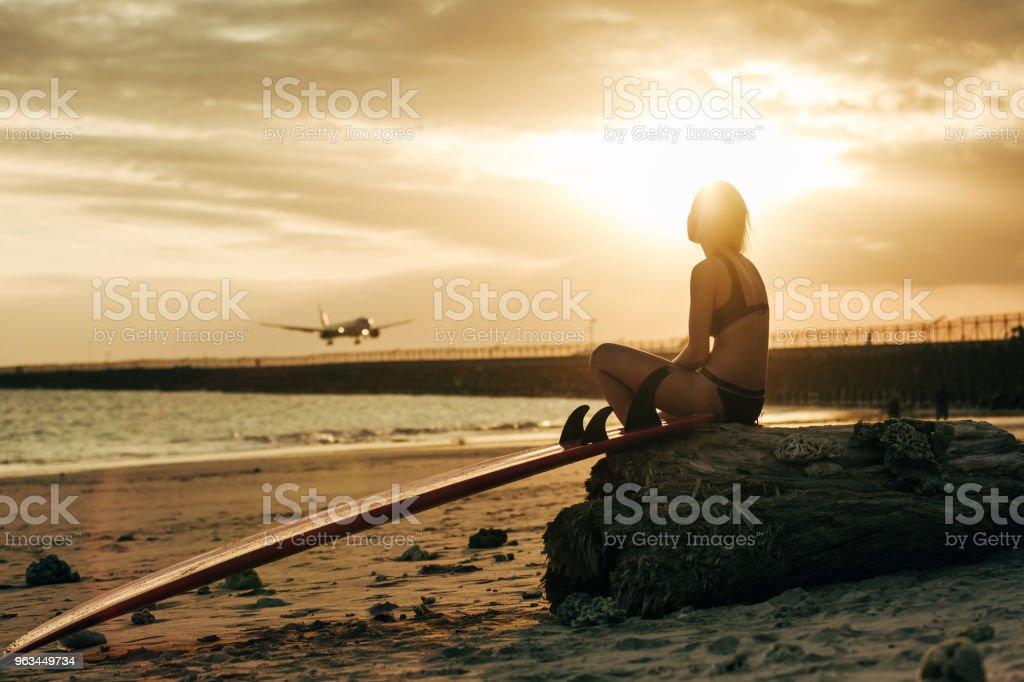 Kvinnan sitter på rock med surfbräda på stranden vid solnedgången med flygplan i himlen - Royaltyfri Avkoppling Bildbanksbilder
