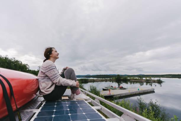Mujer sentada en el techo de la furgoneta camper cerca del lago - foto de stock