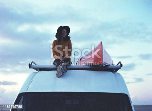 Young Caucasian woman sitting  on roof of camper van  on beach in Denmark