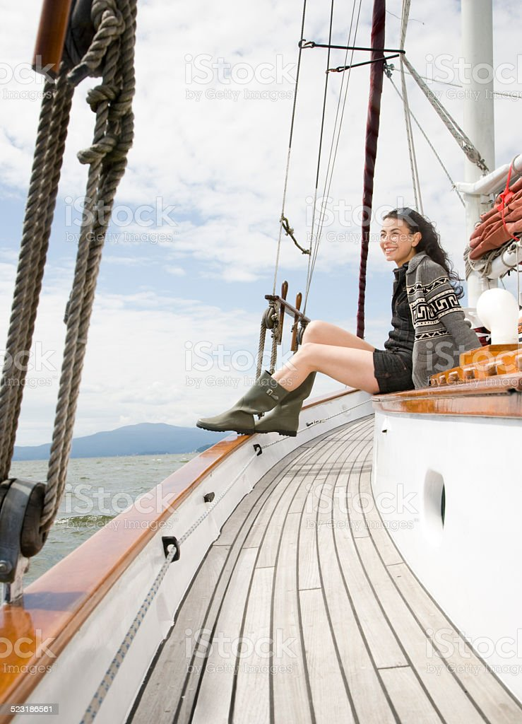 Woman Sitting on Sailboat in Open Water stock photo