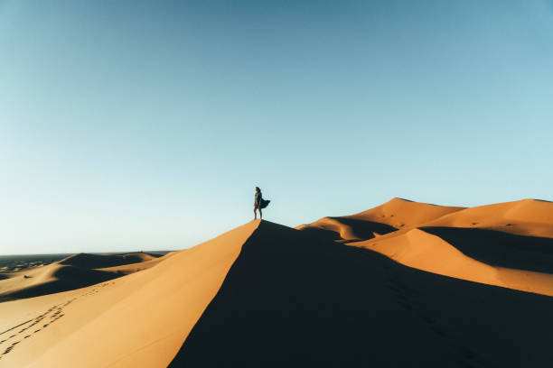 woman sitting on sand  in the desert - sand dune stock photos and pictures