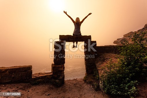 istock Woman sitting on sandstone door arch cliffside Sydney on foggy morning 1139198686