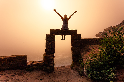 istock Woman sitting on sandstone door arch cliffside Sydney on foggy morning 1139198686