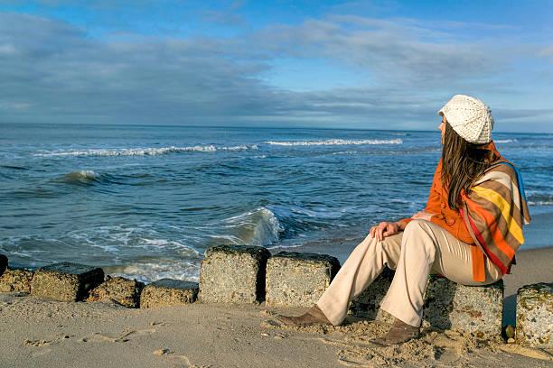 frau sitzt am strand wellenbrecher steine im sonnenlicht - sylt urlaub stock-fotos und bilder