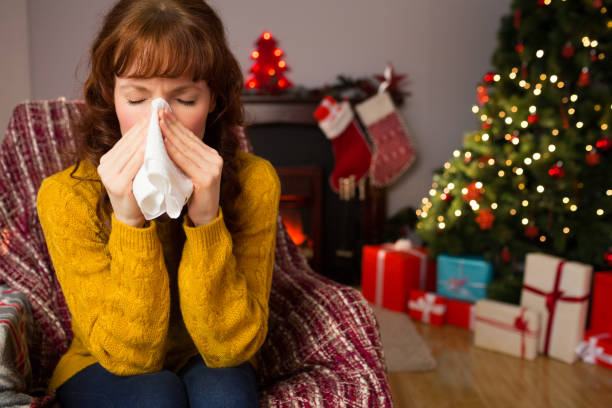 Woman sitting on sofa and blowing her nose at christmas Woman sitting on sofa and blowing her nose at christmas at home in the living room human parainfluenza virus stock pictures, royalty-free photos & images