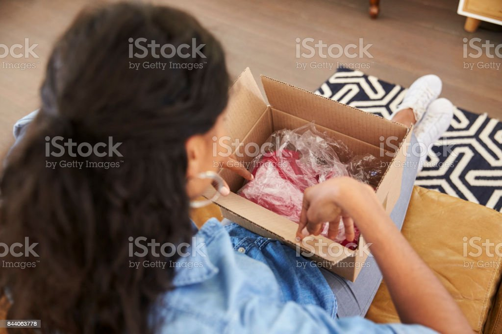 Woman Sitting On Sofa At Home Opening Online Clothing Purchase stock photo