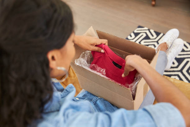 Woman Sitting On Sofa At Home Opening Online Clothing Purchase Woman Sitting On Sofa At Home Opening Online Clothing Purchase clothes in box stock pictures, royalty-free photos & images