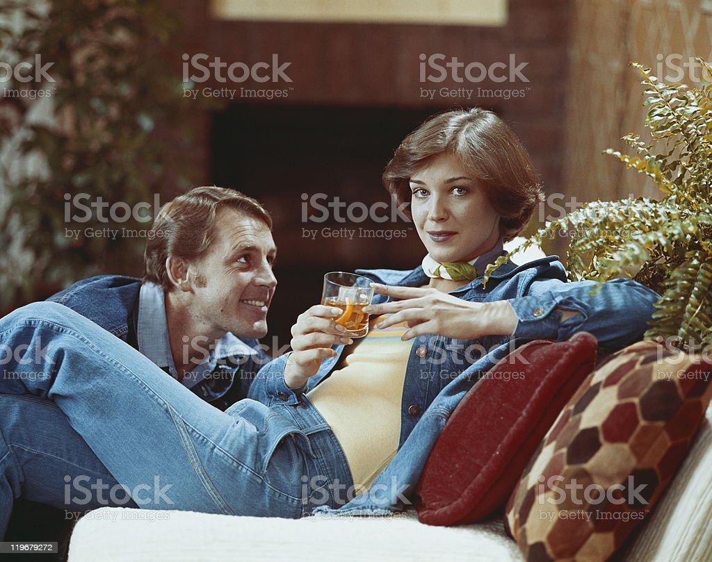 Woman sitting on sofa holding drink stock photo