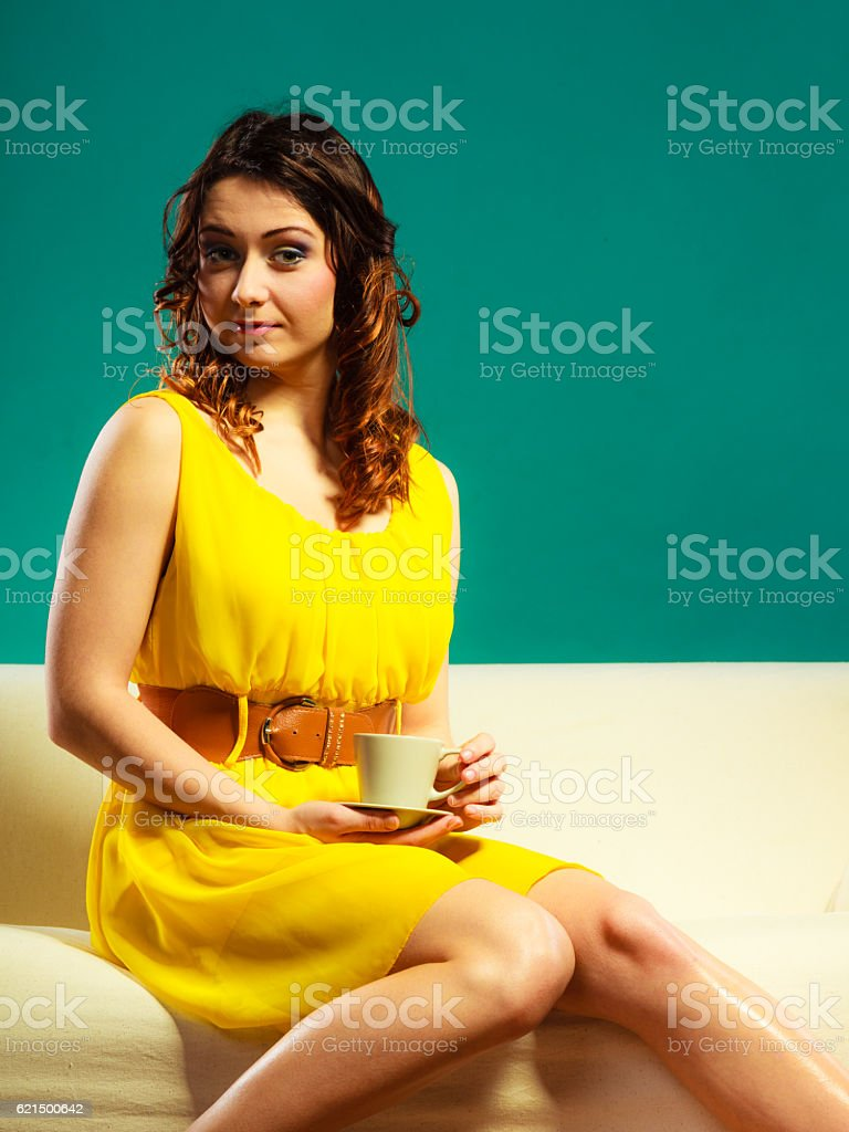 Femme assise sur un canapé-lit pouvant accueillir une tasse à café photo libre de droits