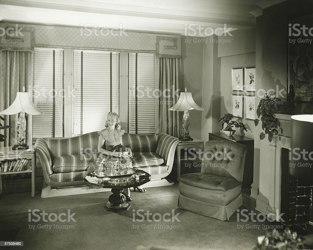 Woman sitting on sofa in stylish living room, (B&W) stock photo