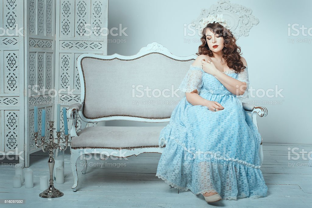 Woman sitting on sofa in the room. stock photo