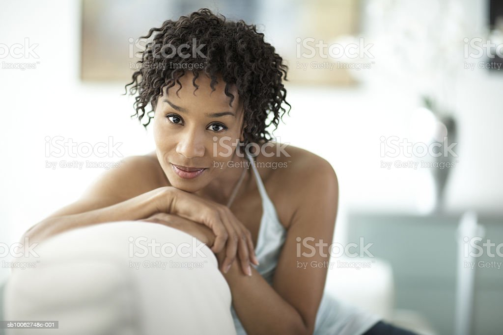 Woman sitting on sofa, smiling, portrait royalty-free 스톡 사진