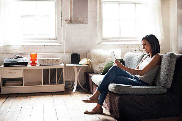 woman sitting on sofa using digital tablet - london themenzimmer stock-fotos und bilder