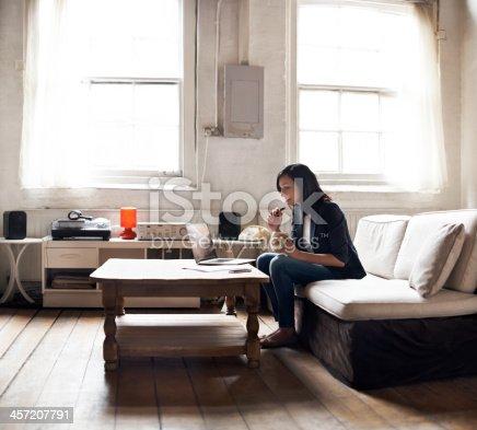 istock Woman sitting on sofa using laptop 457207791