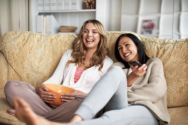 woman sitting on sofa watching tv - bequeme kleidung stock-fotos und bilder